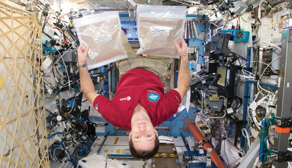 esa astronaut with tomatosphere seed packs