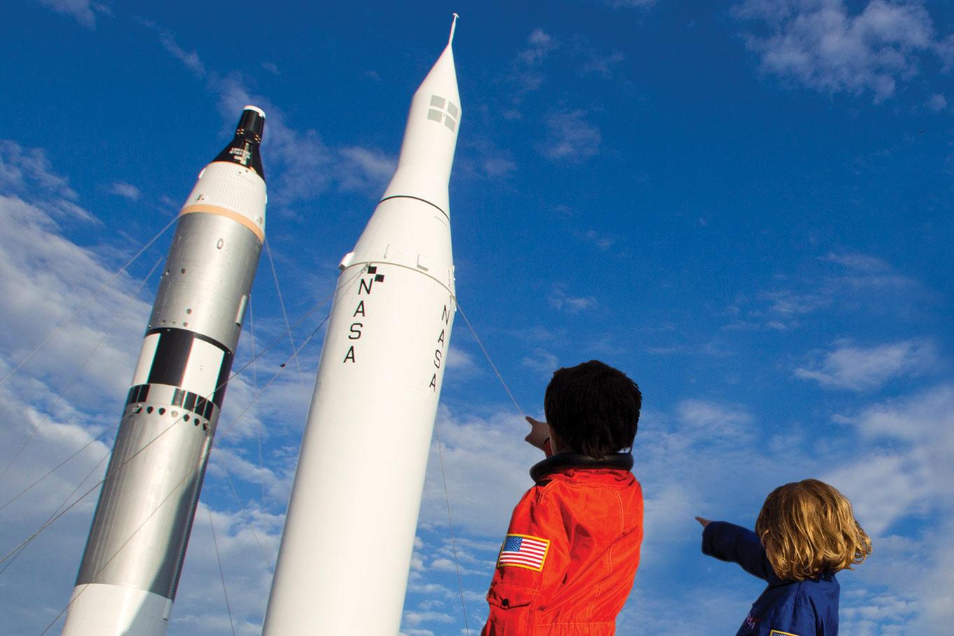 kids pointing rockets blue sky