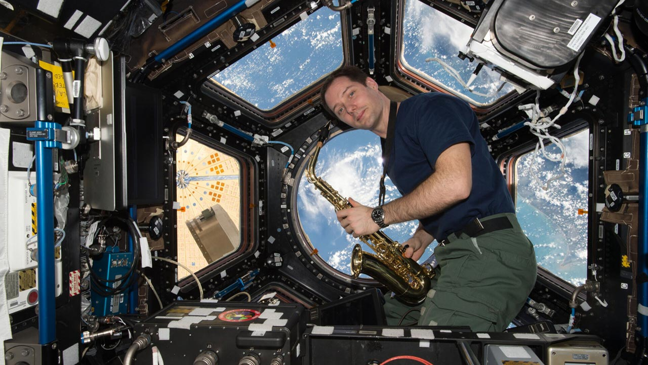 Thomas Pesquet with saxophone in Cupola pillars